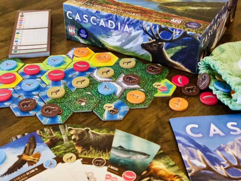 The components found in Cascadia Board Game by AEG and Flatout include wooden wildlife tokens, tiles, wildlife scoring cards and a bag