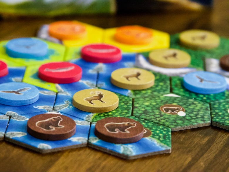 Tiles placement game with beautiful components - wooden tokens with bear, elk, salmon, fox and hawks. Cascadia Board Game by AEG and Flatout