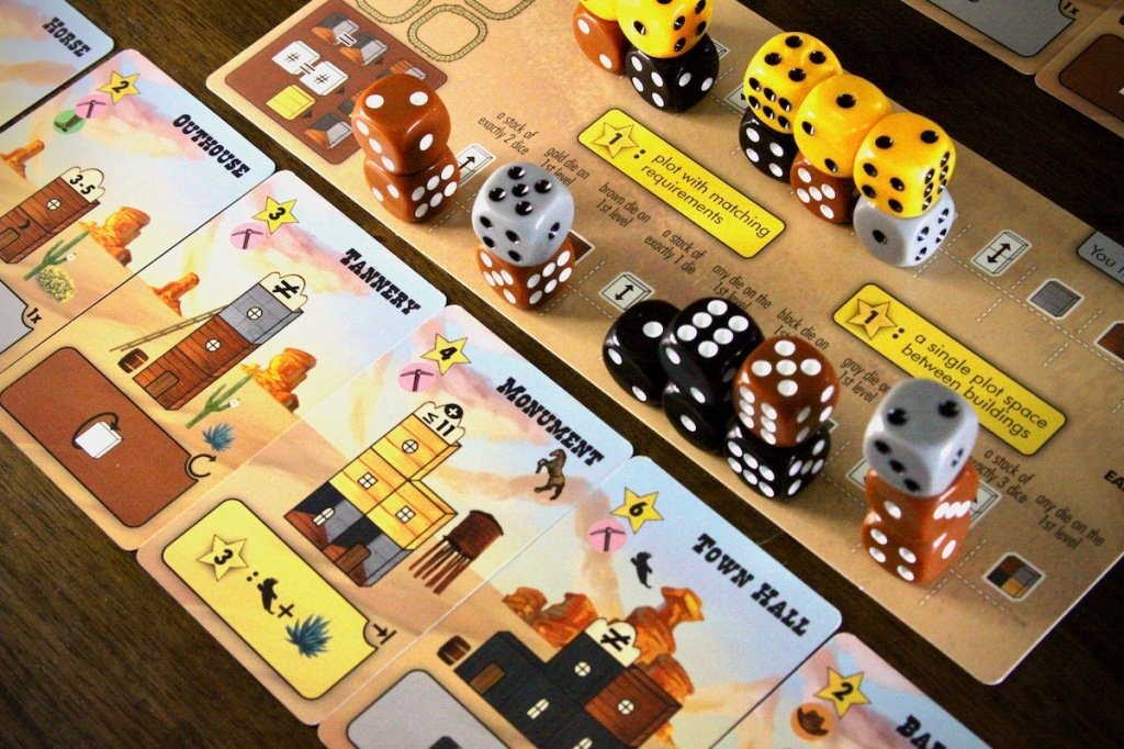 Example of a player mat full of dice buildings and building cards in Tumble Town board game by Weird Giraffe Games