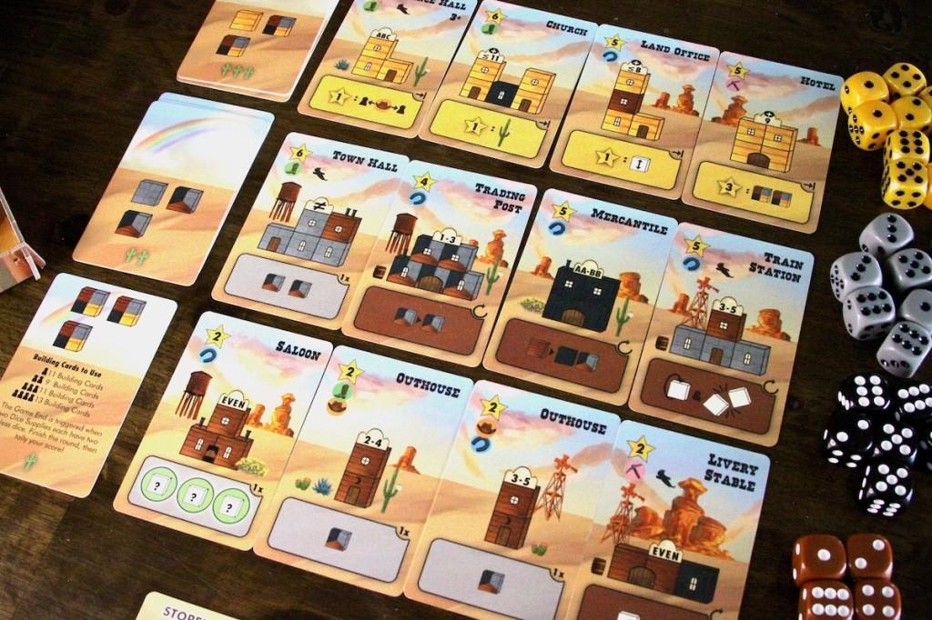 The building card market featuring an outhouse, saloon, mercantile, town hall, and hotel in Tumble Town board game by Weird Giraffe Games