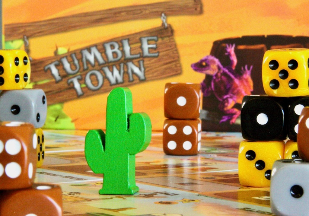 The starting token is a wooden Saguaro cactus and the buildings are made from dice in Tumble Town board game by Weird Giraffe Games